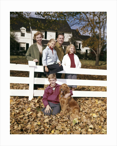 1960s Family with Dog At White Board Fence In Front Of Colonial Style Suburban House by Corbis