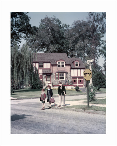 1950s Kids Carry Book Bags Crossing Street By Yellow Stop Sign In Suburban Neighborhood by Corbis