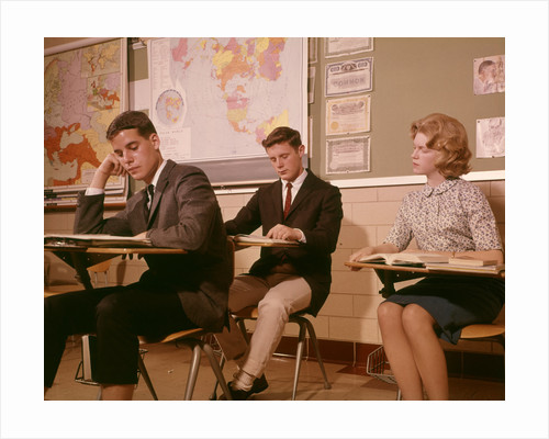 1960s 3 College High School Students Sitting Desk Chairs Reading Studying Classroom by Corbis