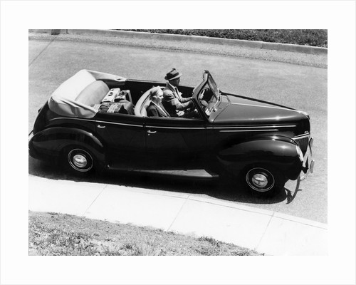 1930s 1940s Couple Driving 1938 Convertible Four Door Sedan Automobile With Luggage In Back Seat by Corbis