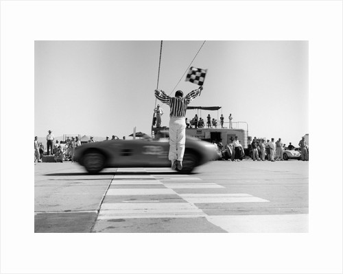 1960s Man Jumping Waving Checkered Flag As Winning Sports Car Crossing The Finish Line by Corbis