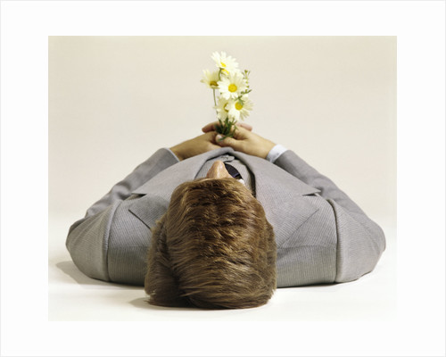 1970s Man Lying Down Pushing Up Daisies by Corbis
