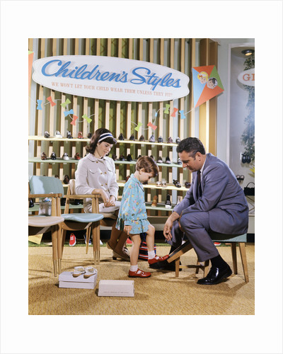 1960s 1970s Mother Watching Salesman Fit Shoes On Daughter In Shoe Section Of Department Store by Corbis