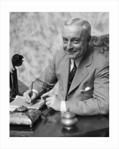 1920s 1930s Man Businessman,Salesman Sitting At Desk Smoking Cigar Writing A Memo by Corbis