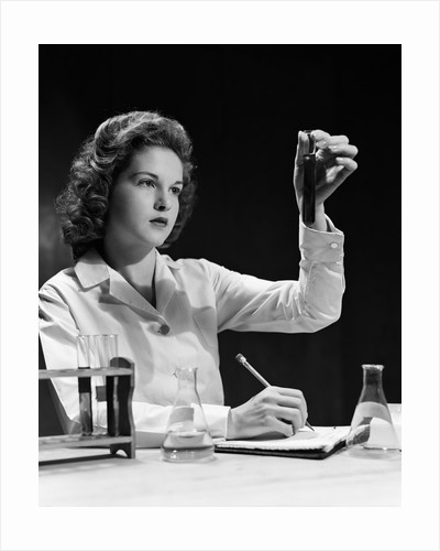 1940s Student Nurse Holding Up Test Tube While Taking Notes In Science Class by Corbis
