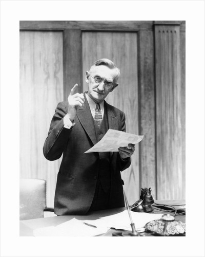 1930s Elderly Man In Office Standing Behind Desk Gesturing With Raised Finger by Corbis