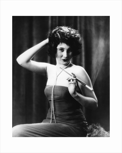 1920s Woman Wearing Strapless Gown String Pearls Holding Cigarette Holder Hand On Back Of Head by Corbis