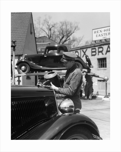 1930s Service Station Attendant In Cap and Coveralls Pouring Water From Spouted Can Into Automobile Radiator by Corbis