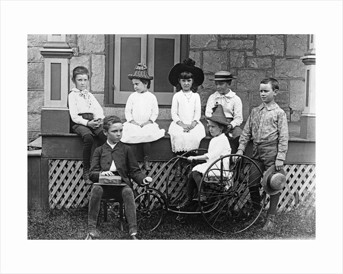 1890s 1900s Seven Children Sitting On and Around Porch One Girl On Old Fashioned Tricycle by Corbis