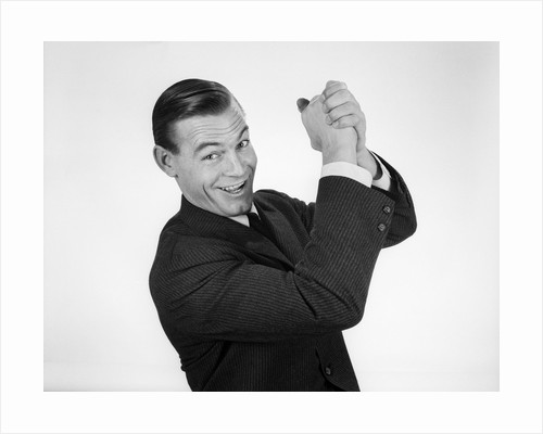 1950s 1960s Businessman Hands Clasped Overhead In Successful Winner Symbolic Sign by Corbis