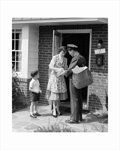 1950s Suburban Mom At Home Front Door With Son Watching Receiving Package From Mailman by Corbis