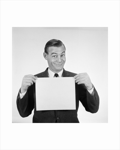 1950s 1960s Man Funny Facial Expression Holding Up Blank Empty Sheet Paper Placard Sign by Corbis