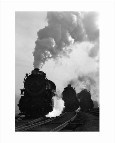 1930s 1940s Head-On View Of Three Steam Engines Silhouetted Against Billowing Smoke And Steam Outdoor by Corbis