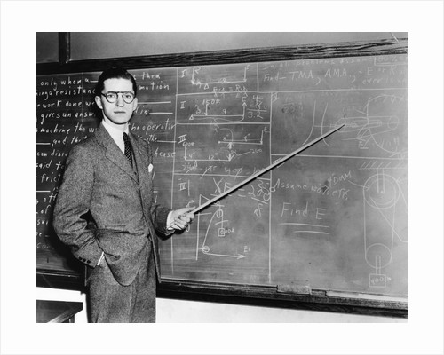 1930s Man Teacher Looking At Camera With Pointer At Blackboard by Corbis