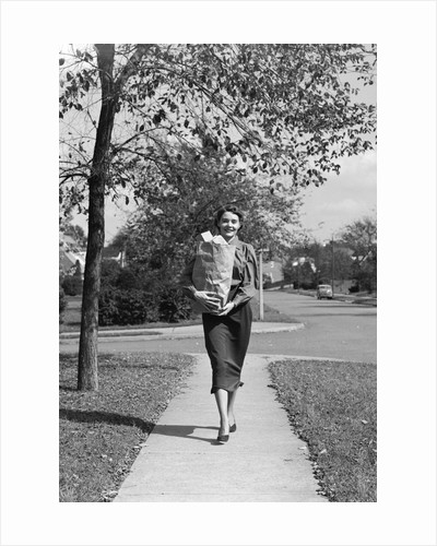 1950s Woman Walking On Sidewalk Carrying A Grocery Bag Full Of Food by Corbis
