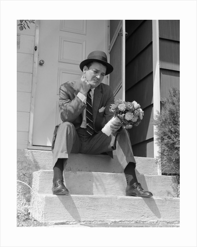 1950s Man In Suit And Hat Holding Flowers Sitting Outside Front Door On Steps Looking Sad by Corbis