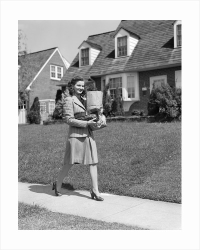 1940s Woman Walking Shopping Carrying Grocery Bag On Suburban House Sidewalk by Corbis