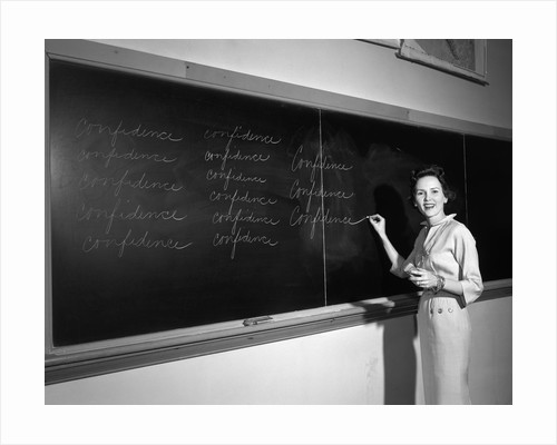 1950s Teacher In Front Of Classroom Writing Confidence On Blackboard by Corbis