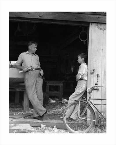 1930s Man Father Holding Hand Tools Talking To Boy Son Leaning In Doorway Of Boat Shed by Corbis