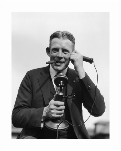1920s Portrait Of Businessman Talking On Candlestick Phone Smoking Cigar Office Indoor by Corbis