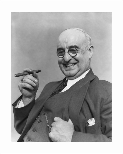 1930s Elderly Businessman In 3-Piece Suit and Glasses Leaning Back With Cigar In Hand by Corbis