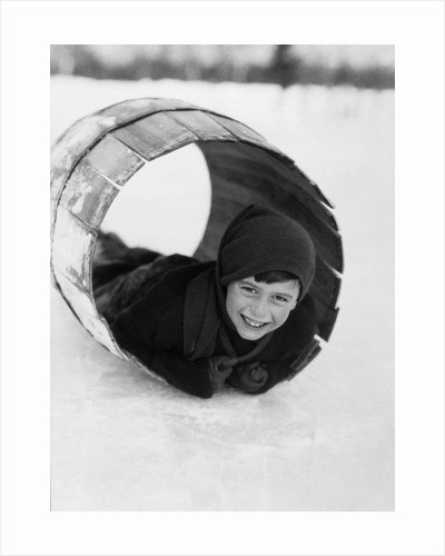 1920s Boy Playing Lying In Snow Rolling In Wooden Barrel by Corbis