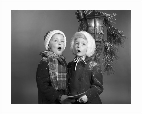 1960s Boy And Girl Singing Christmas Carol Together Under Snowy Outdoor Porch Light by Corbis