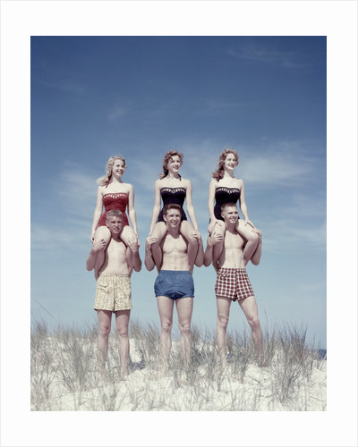 1950s 3 Teen Couples Standing On Sand Dune Girls Sitting On Guys Shoulders by Corbis