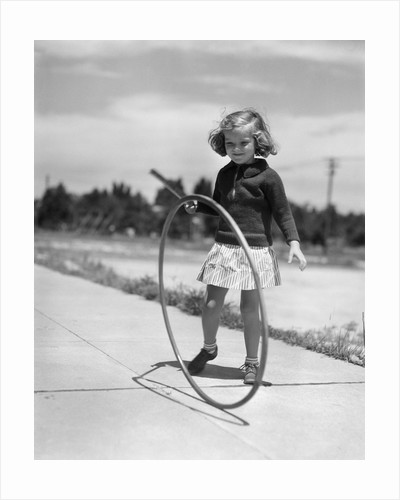 1930s Girl Playing With Hoop And Stick On Sidewalk by Corbis