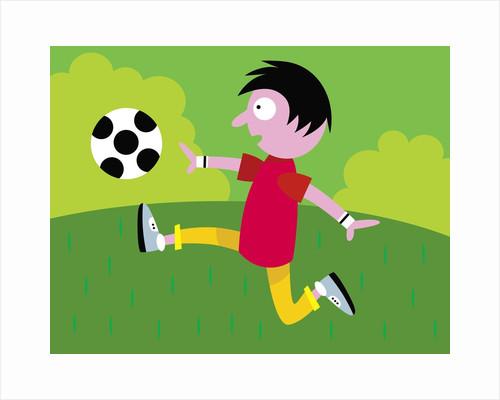 Boy kicking soccer ball by Corbis