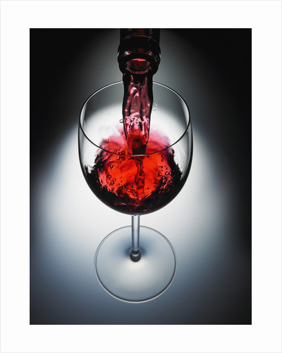 Wine poured in glass by Corbis