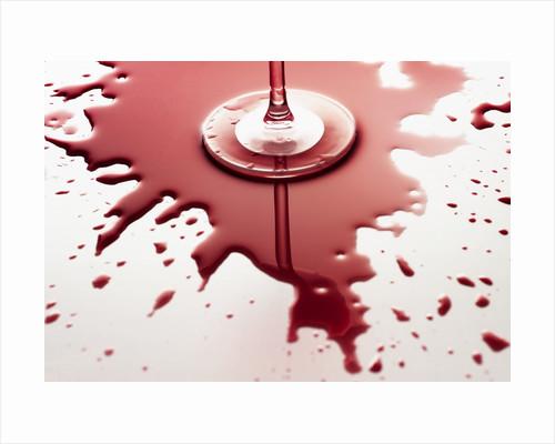 Red wine spilled around glass by Corbis