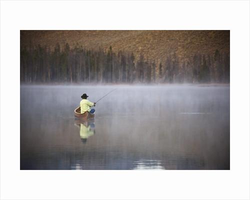 Man fishing on foggy lake by Corbis