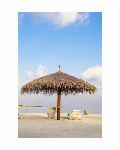 Beach chairs and umbrella at the beach by Corbis