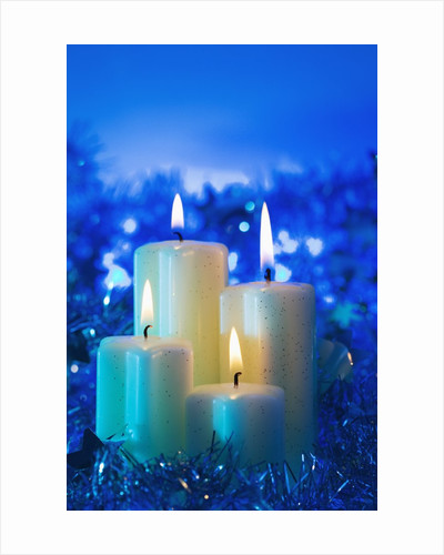 Lighted candle arrangement surrounded by holiday decorations by Corbis