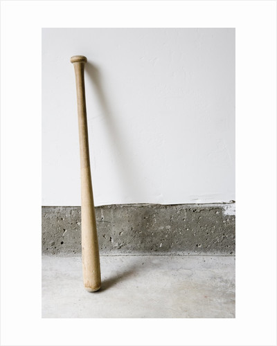 Detail of wooden baseball bat against white and concrete wall. by Corbis