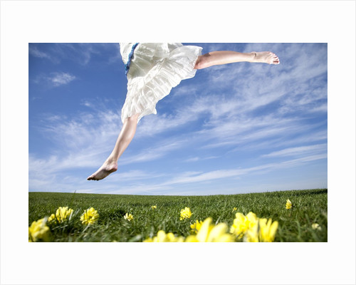 Young woman in park jumping on lawn by Corbis