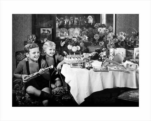 Brothers, ages 8 and 3, pose with birthday presents, ca. 1949 by Corbis