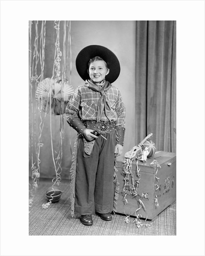 Ten-year-old boy poses in a cowboy outfit, ca. 1951 by Corbis