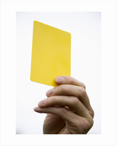 Hand holding yellow card by Corbis