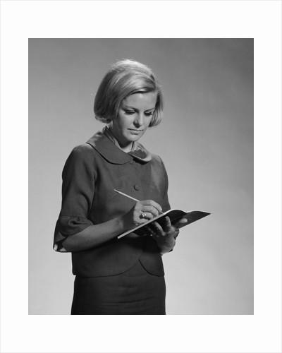 Blond woman secretary teacher taking notes by Corbis