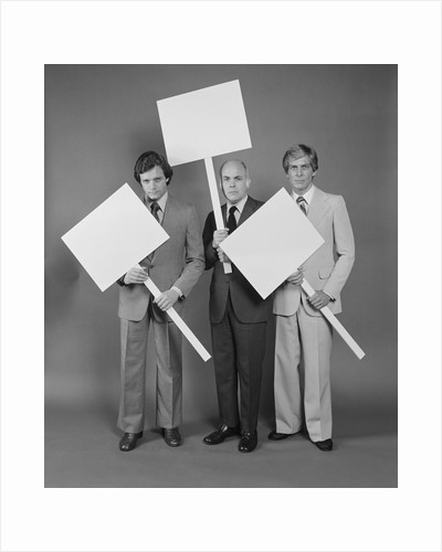 Trio of businessmen carrying blank signs by Corbis