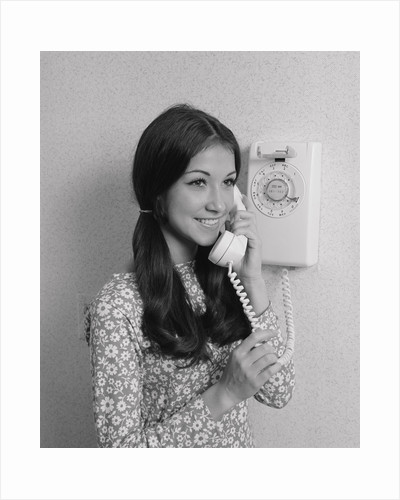 Smiling teenage girl talking on rotary wall telephone by Corbis