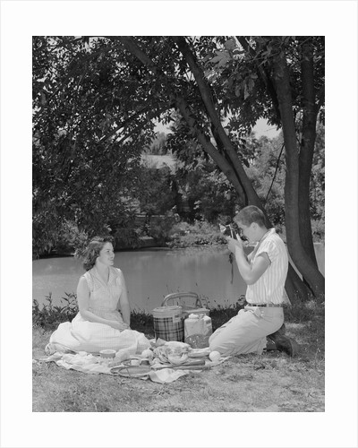 Teenage couple picnic boy taking photograph of girl outdoors by Corbis