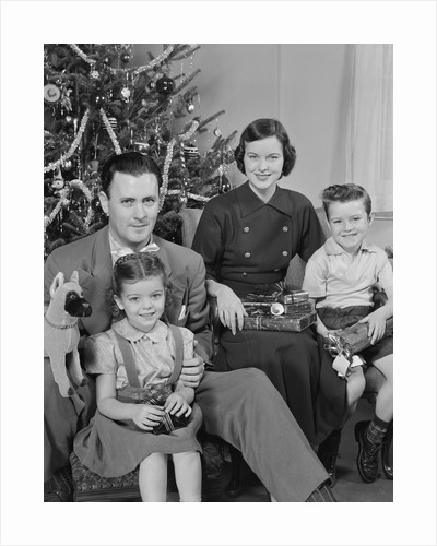 Family portrait by christmas tree by Corbis