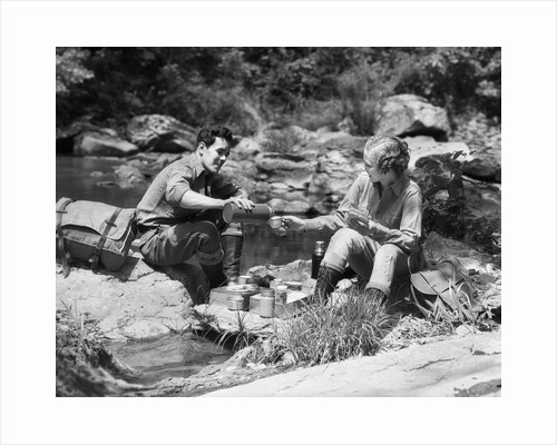 Couple having picnic sitting on rocks by stream man pouring drink for woman from thermos by Corbis