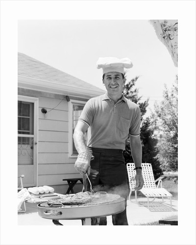 Smiling man outdoors in backyard patio wearing chef hat cooking steaks hot dogs on grill by Corbis