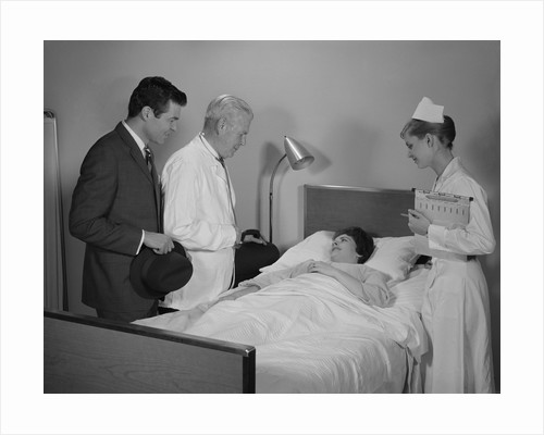Doctor nurse husband talking with female patient in hospital bed by Corbis