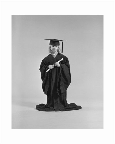 Girl wearing graduation cap gown holding diploma by Corbis