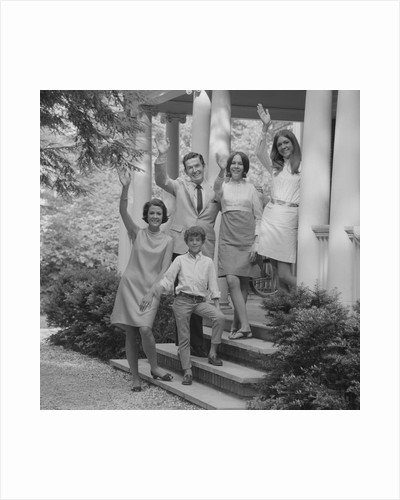 Family group of people standing on steps of house waving by Corbis